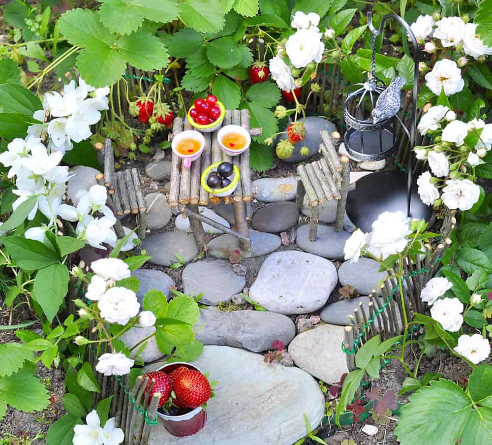 Cute fairy picnic scene with little stick fairy furniture, berries on a small stone patio surrounded by flowers.