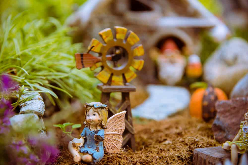 Close up photo of a fairy village with little windmill, house, pumpkin surrounded by plants and flowers.