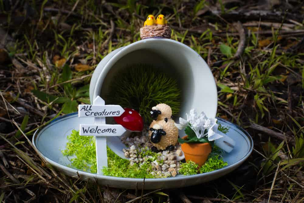 Small decorative garden schene built in plate and includes white pot with miniature lambs, chicks, welcome sign and small flowers.