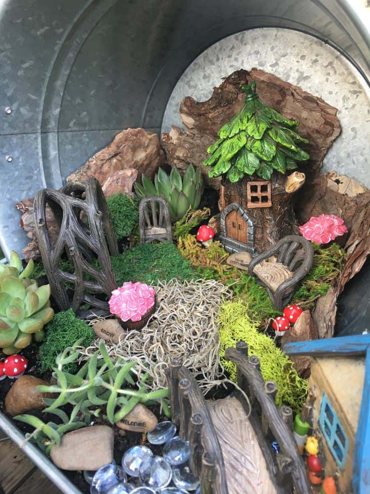 Fairy scene with house, bridge, chair and archways built in large steel bucket.