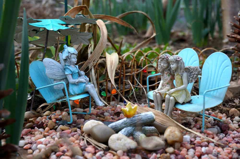 Small fair chairs with fairies in small pebble garden.