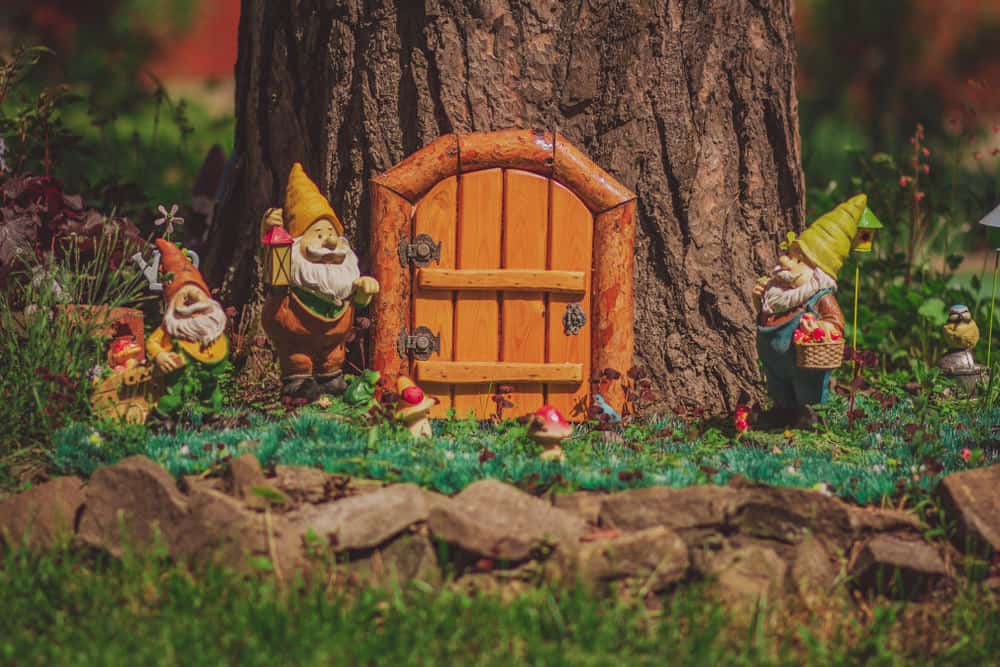 Small gnome garden with house in stump and garden gnomes placed around the base of the stump.