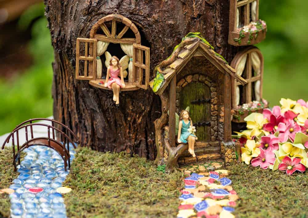 Fabulous stump fairy house with windows, shutters, front door and porch, flowers, creek with bridge and colorful walkway.