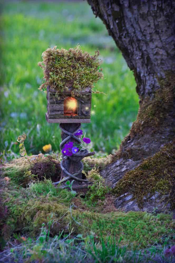 Log fairy house on small stump with a light.
