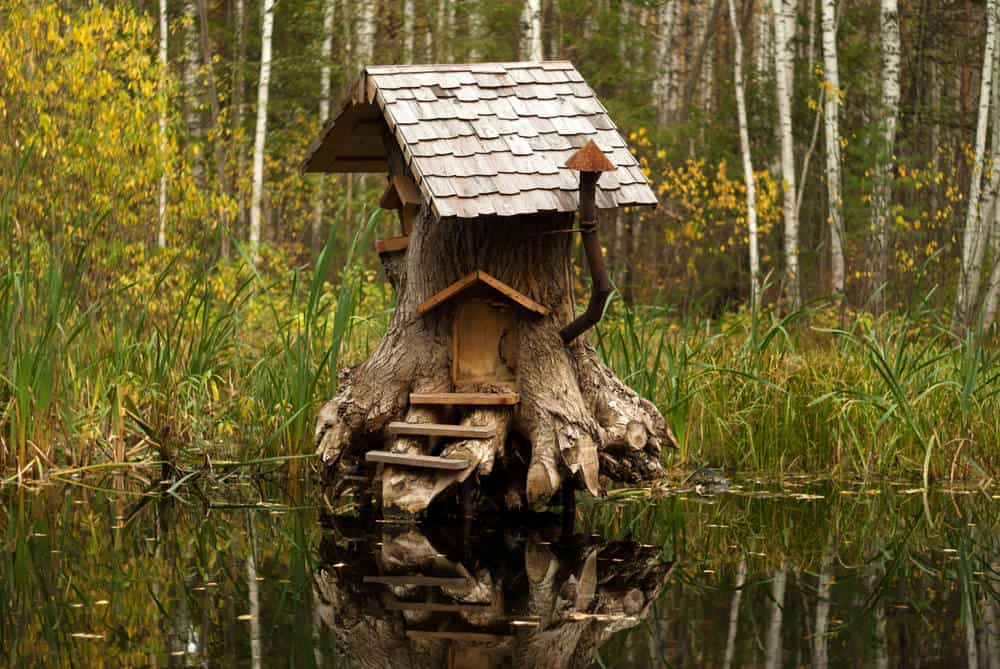 Old stump converted into fairy house with front steps, door and wood shingle roof along with wood shingles on gabled roof.