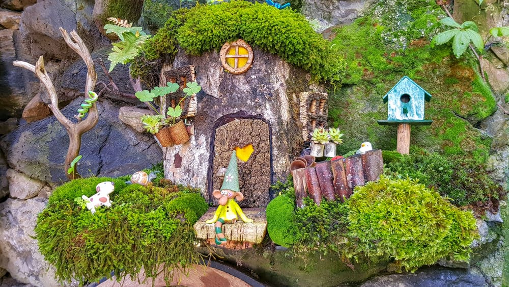 Fairy house built into stump with front stoop, small birdhouse and miniature dog and snail. Very nice decorative garden scene.