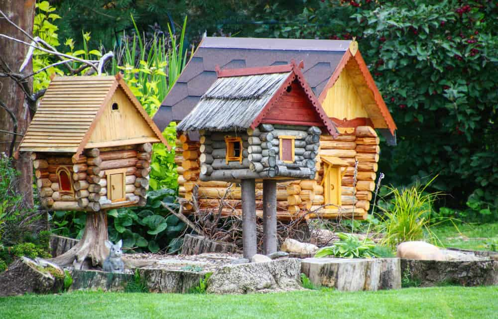 Spectacular miniature log fairy houses built up on small stumps.