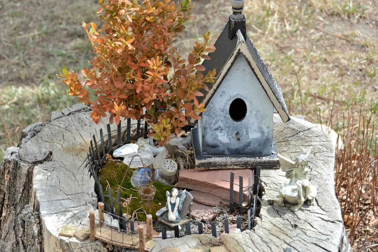 Fairy house, bridge and furniture built into stump.