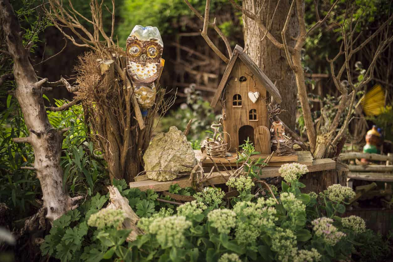 Spectacular wood fairy house and decorations built into garden.