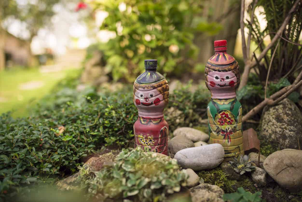 Two decorative miniature figures in small garden.