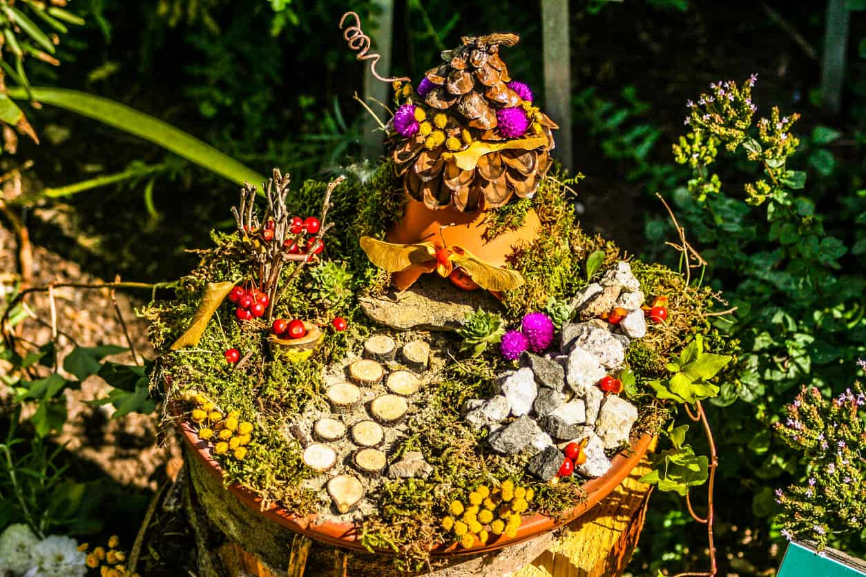 A fairy house in a tree stump with a wood cut walkway, berries, little flowers and other decorative elements. This is a realy beauty.