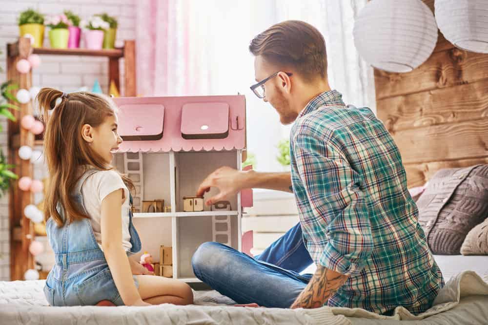 father and daughter playing with dollhouse