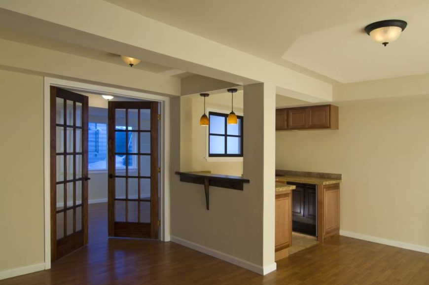 A finished basement yet to be decorated and furnished. It features hardwood flooring, a small bar area and French doors.