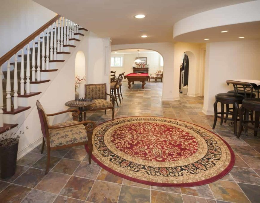 A glamorous entry to the home's basement featuring a classy rug and seats along with a small coffee table set on the side.