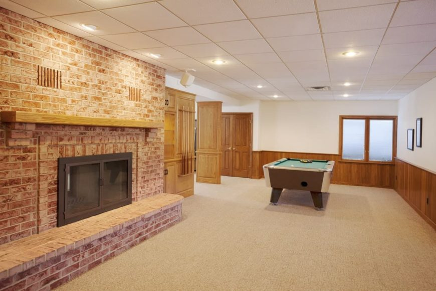 Spacious basement with a fireplace made with bricks along with a billiards table set. The room features carpet flooring.