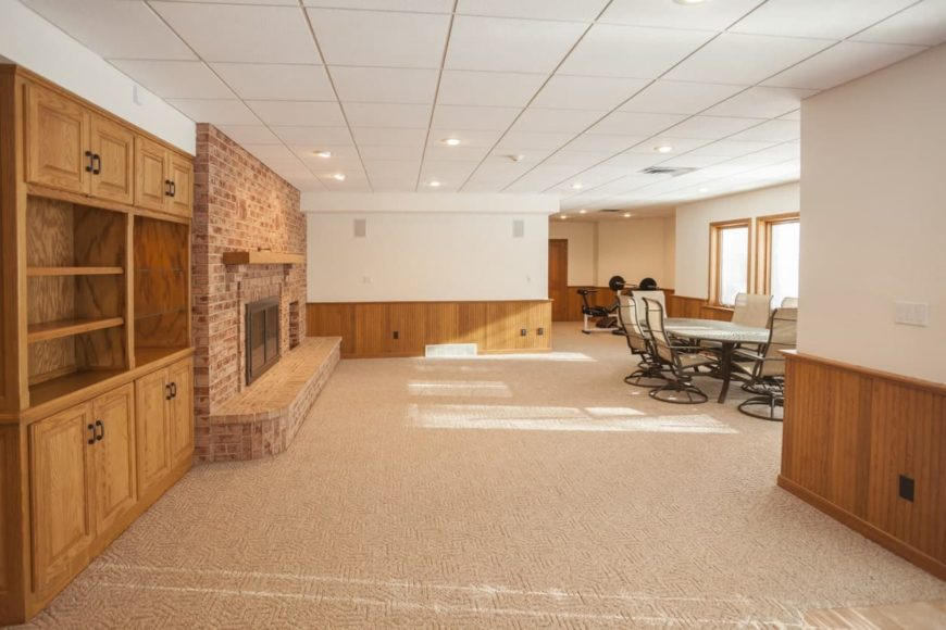 This spacious finished basement features a large brick fireplace along with an office table and a small weight lifting area.