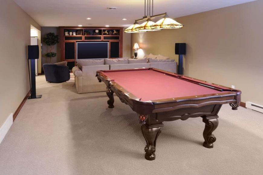 A media room with a billiards table set on the carpet flooring and lighted by a gorgeous pendant lighting.
