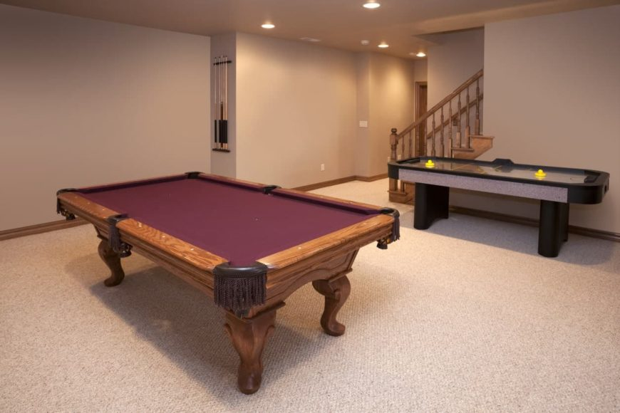 A basement turned game room with billiards table and an air hockey table both set on the carpet flooring.