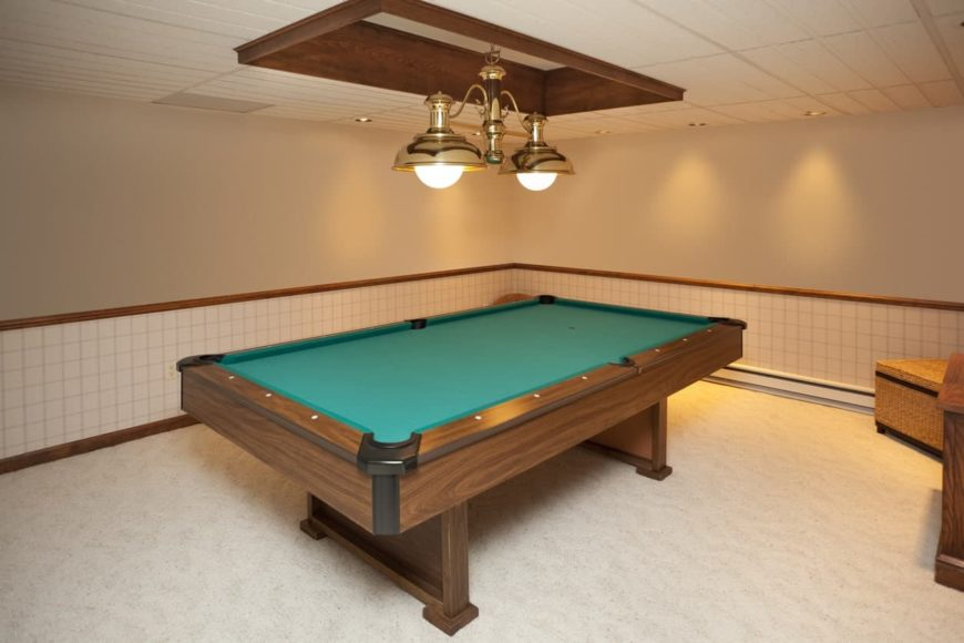 A close up look at this billiards table set on the white carpet flooring and lighted by classy pendant lights.