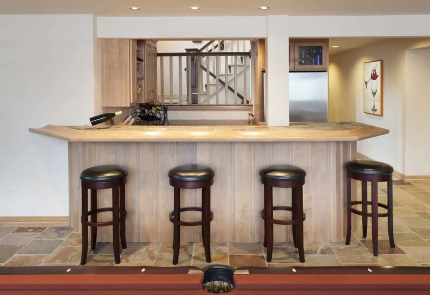A focused shot at this finished basement's bar area with a classic set of bar stools set on the tiles flooring.