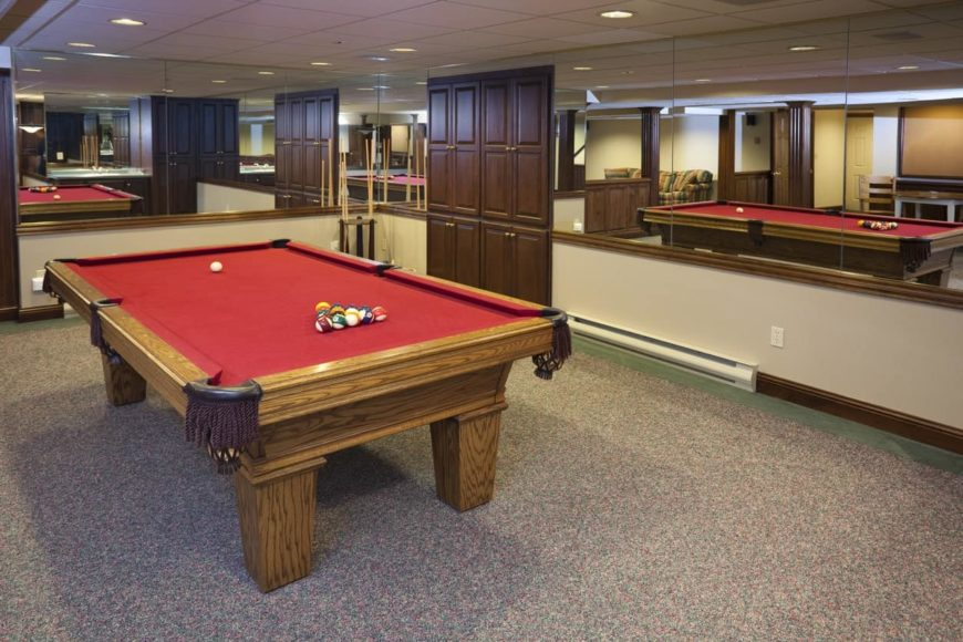 A game room featuring a traditional billiards table set with a red cloth. The massive rug looks absolutely charming as well.