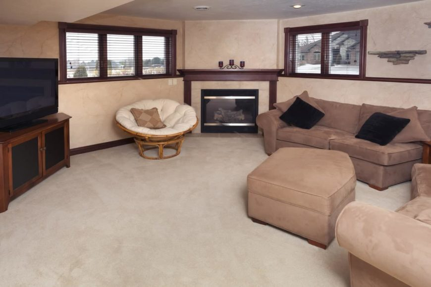 A formal living room featuring a cozy sofa set and a stylish fireplace along with carpet flooring.