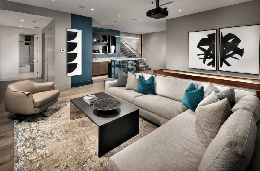 Modern finished basement with a living space featuring a modish sofa set and very attractive wall decors. There's a stylish bar area as well.