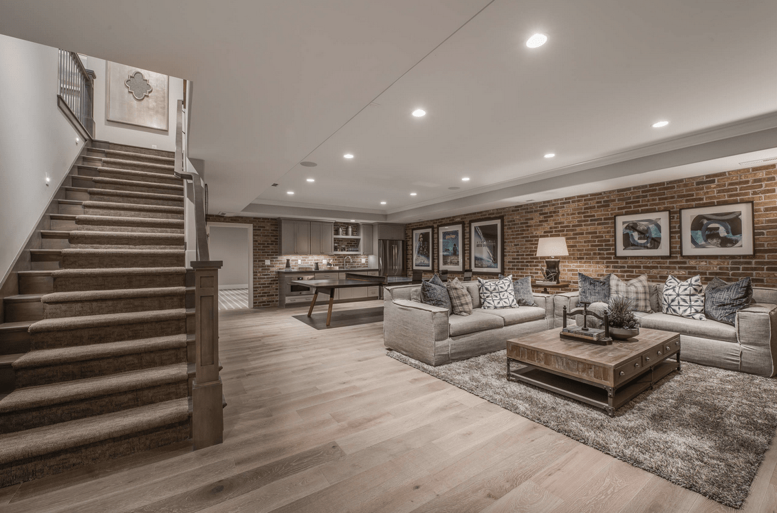 A finished basement with a rustic straight staircase and hardwood flooring. The brick wall adds style to the room.