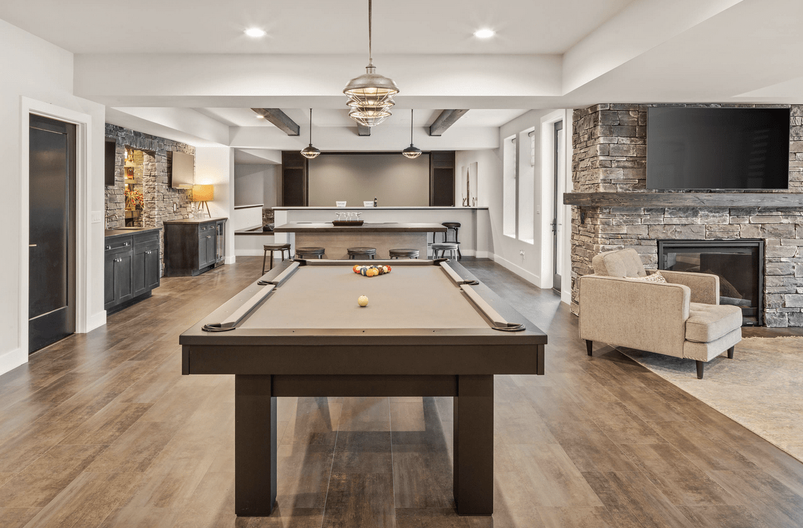 A close up look at this finished basement's billiards table set on top of the hardwood flooring.