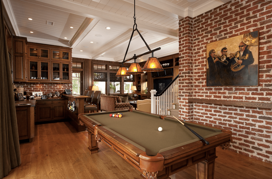 A man cave with a bar area and a living space, along with a billiards table set lighted by a classy pendant lighting.
