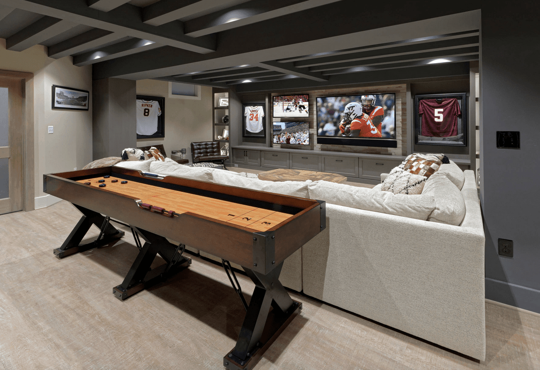 A stylish man cave featuring an American Football inspired living space and an elegant bar area. The room also boasts a stunning ceiling.