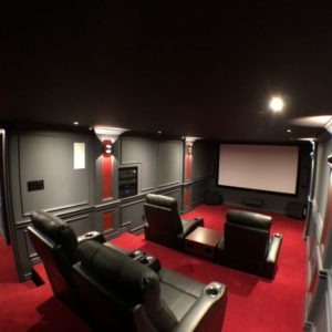 Photo of the finished DIY home theater from behind showcasing the 4 seats built on stadium-like seating platform all having a great view of the screen.