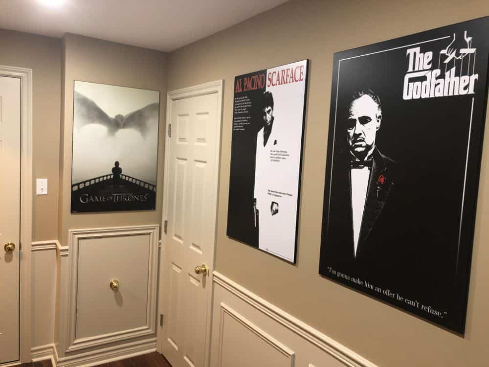 Photo of the outer area leading into the home theater with movie posters and nice wall paneling.