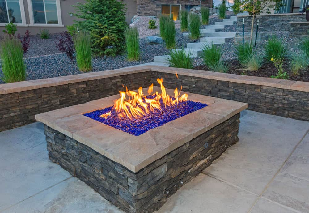 L-shaped brick bench around a rectangle propane fire pit table on flagstone patio.