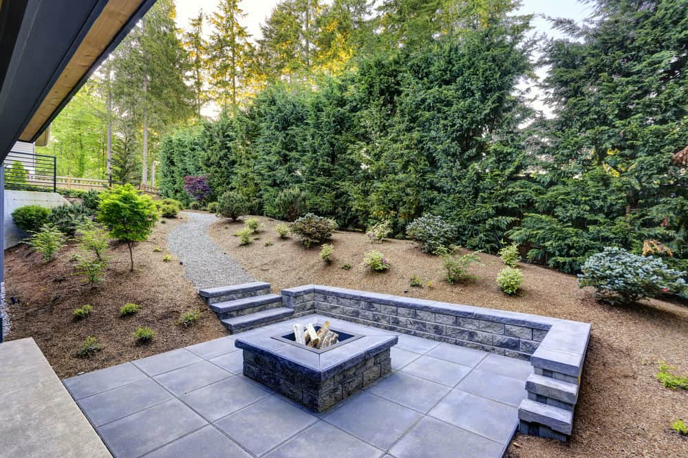 Custom built gray stone l-shaped bench around a square custom built-in above-ground wood-burning fire pit on gray-blue flagstone patio.