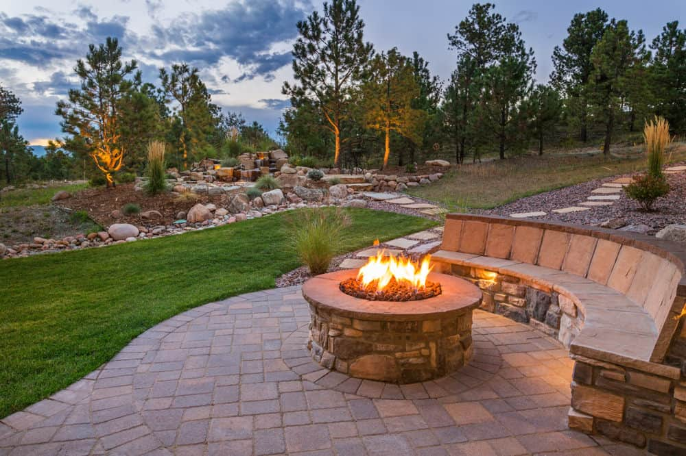 Here's a relatively comfortable built-in stone patio bench with back around a stone circular propane fire pit on backyard patio.
