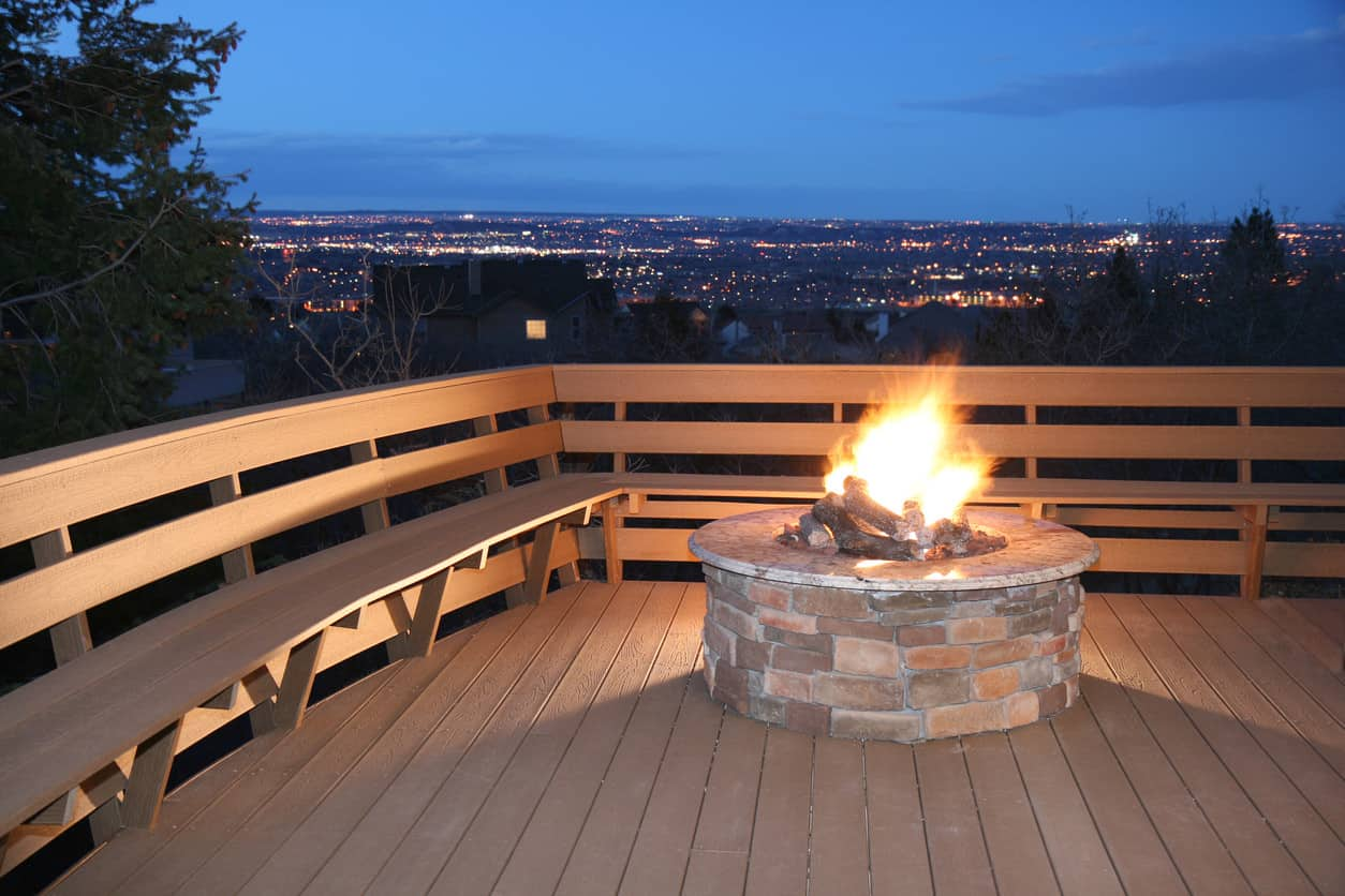 Wood deck bench with back in l-shape around a red brick above-ground fire pit.