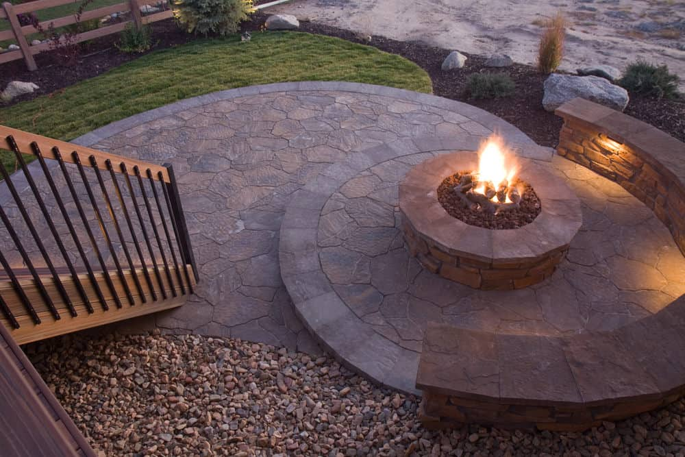 Semi-circle red brick patio bench on a circular patio around a circular propane fire pit.