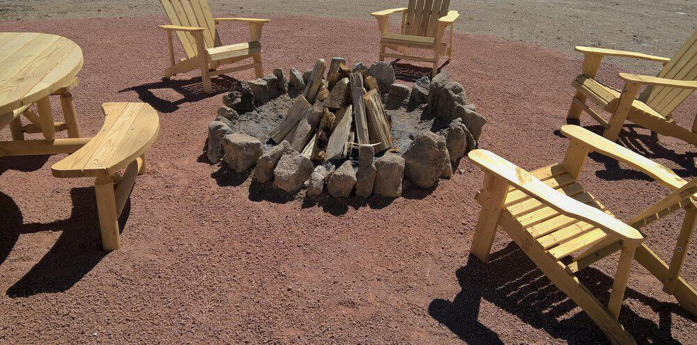 Adirondack chairs around a rock-style fire pit. Seating includes benches around an adjacent picnic table.