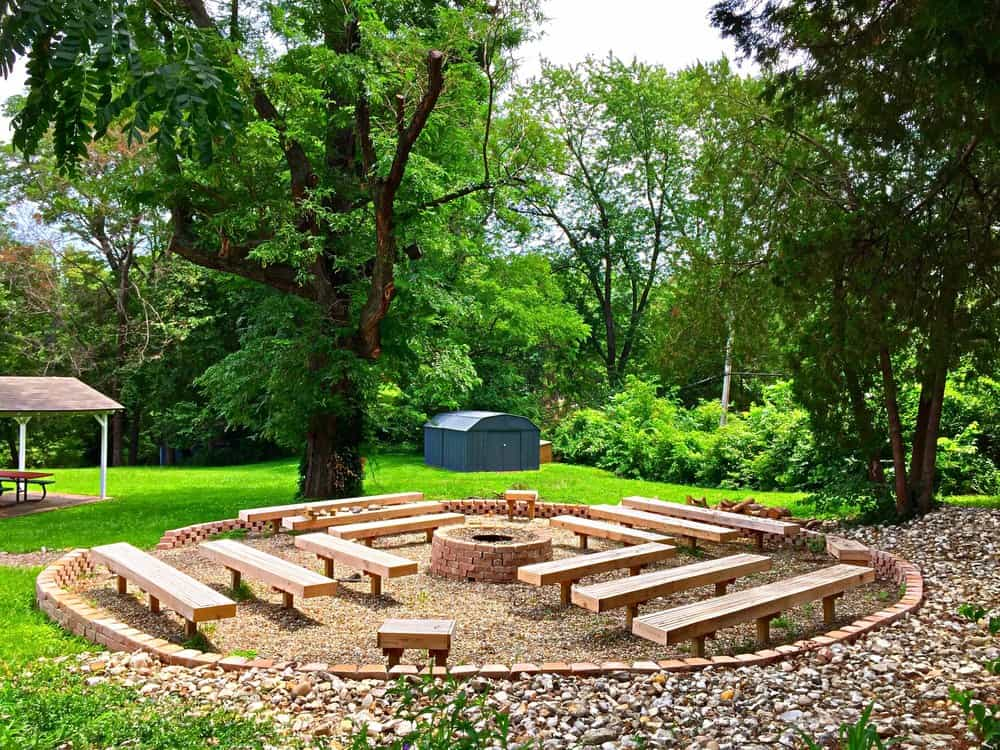 Bench fire pit seating for a large gathering of people with several rows of benches around a circular fire pit in sunken fire pit area.