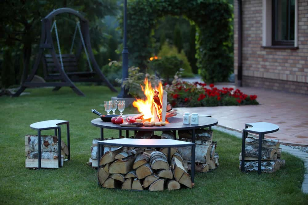Here's an example of metal benches doubling as wood storage as seating around a matching round fire pit.