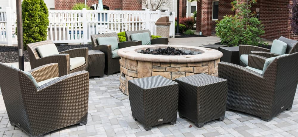 6 contemporary patio armchairs with several matching side-tables around a huge patio fire pit. The side tables could double as additional seating.