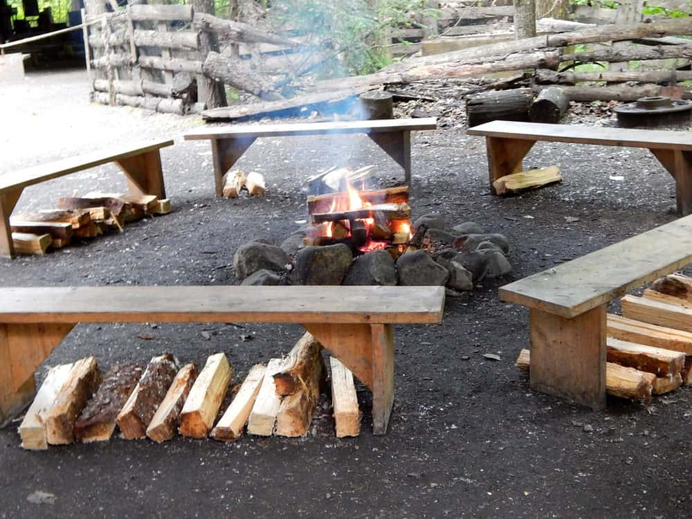 Simple DIY wood benches placed around a rock fire pit. This is about as simple as it gets for DIY fire pit seating.
