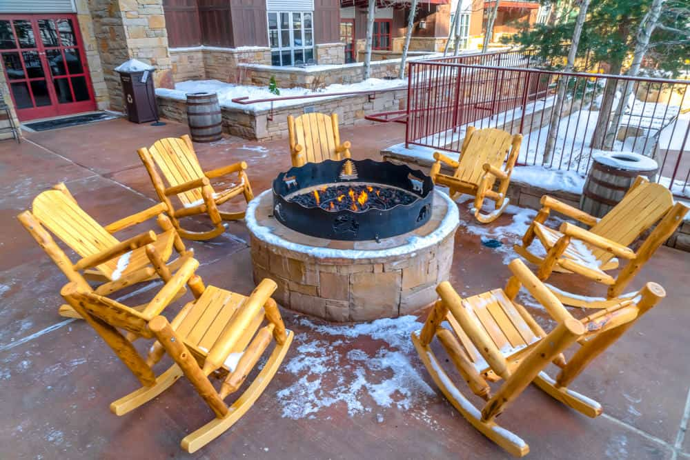 Here's an example of rustic log-style rocking chairs placed around a large patio fire pit.