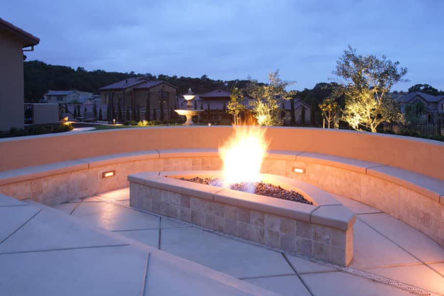 Elaborate stone built-in patio bench wrapping around a propane fire pit.