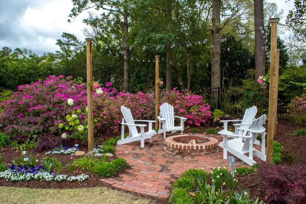 White Adirondack chairs circle a round brick fire pit on a garden brick patio.