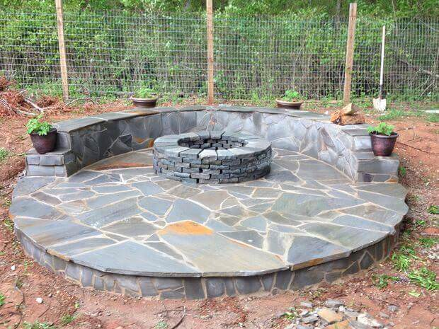Stunning gray flagstone circular fire pit patio with curved matching flagstone built-in bench.