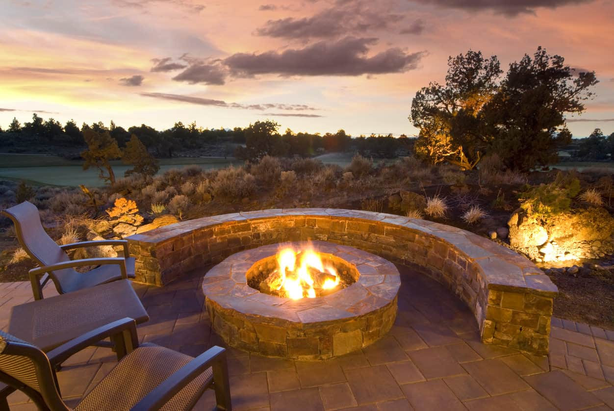 Curved brick bench around a circular brick fire pit on red brick patio. Patio chairs complement the bench.