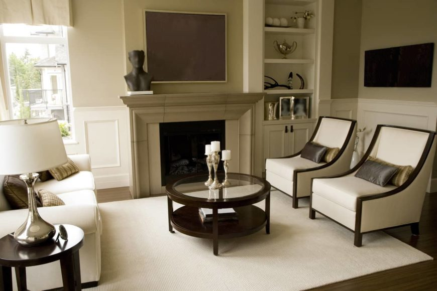 This is a formal living room for accepting guests. It has a circular glass-top coffee table with a dark wood frame that stands out against the white area rug but matches the dark hardwood flooring. This flooring is contrasted by the white sofa and the white cushions of the pair of cushioned chairs.