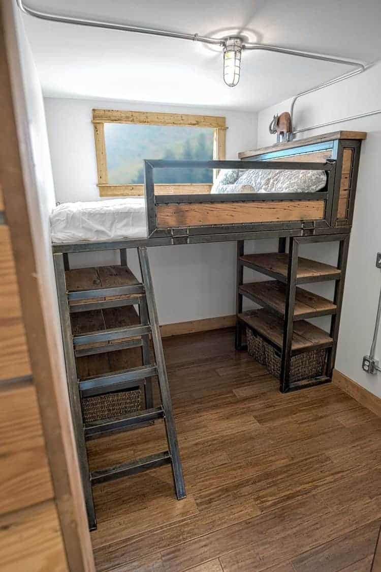 Twin-size loft bed with storage underneath inside tiny container home.